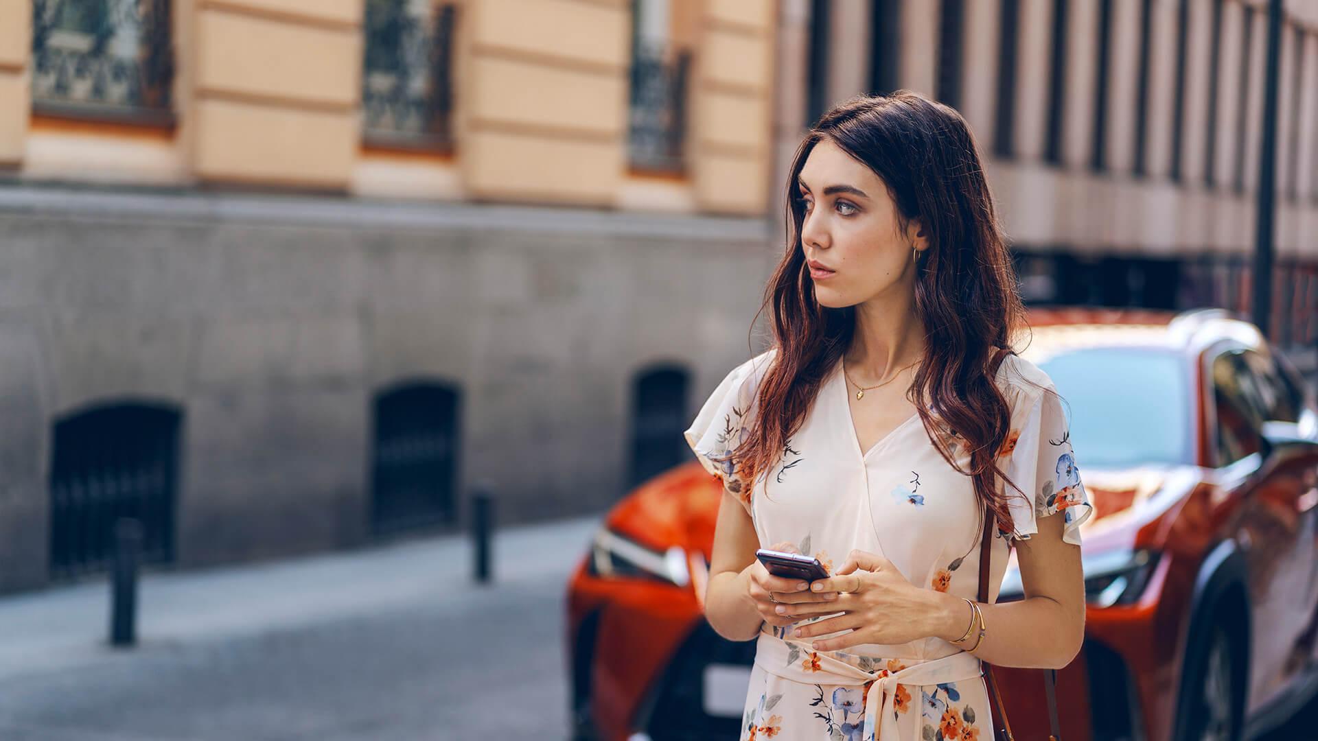 Junge Frau mit Smartphone vor Lexus UX Hybrid