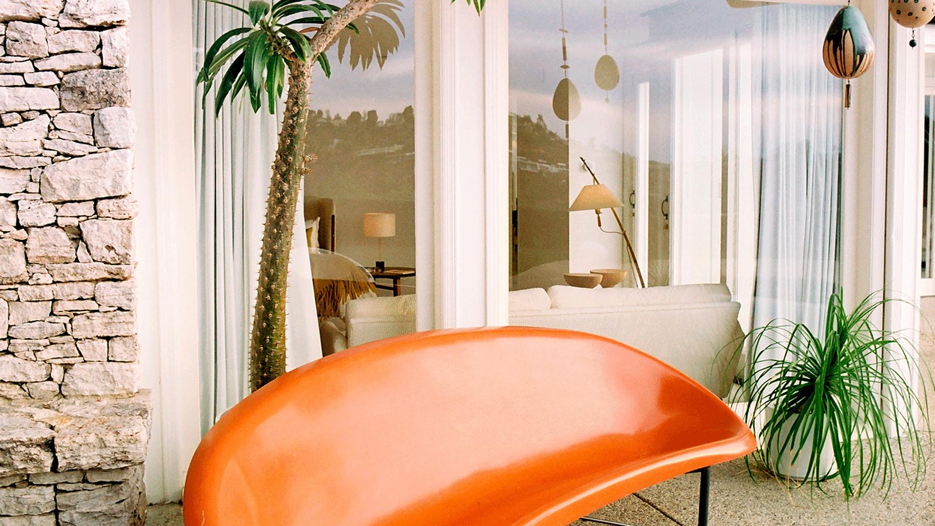Sofá de terraza vintage en tonos naranjas junto a pequeña palmera