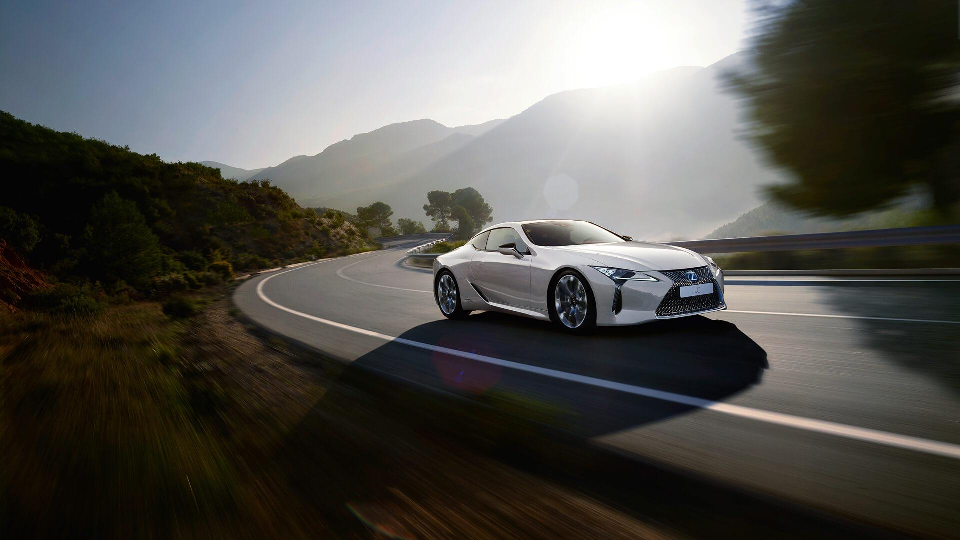 Hvit Lexus LC 500h sportssedan selvladende hybrid kommer kjørende oppover i et landskap med trær og fjell
