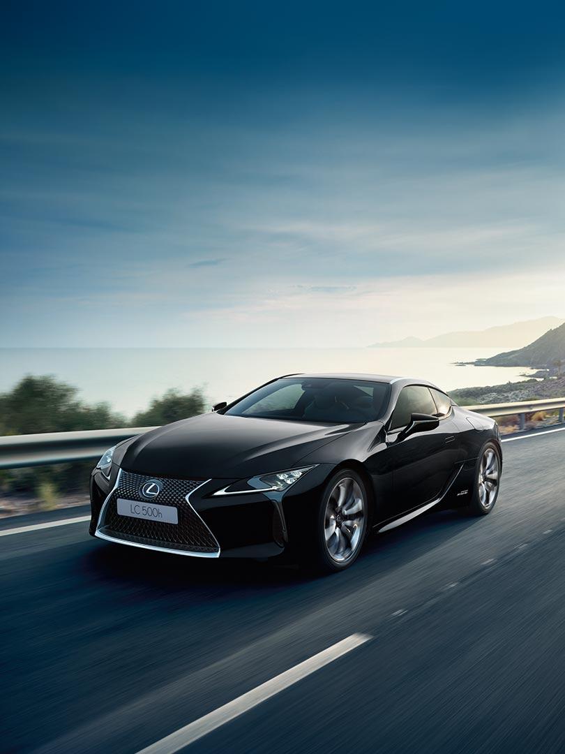 Svart Lexus LC 500h sportssedan selvladende hybrid kommer kjørende mot oss