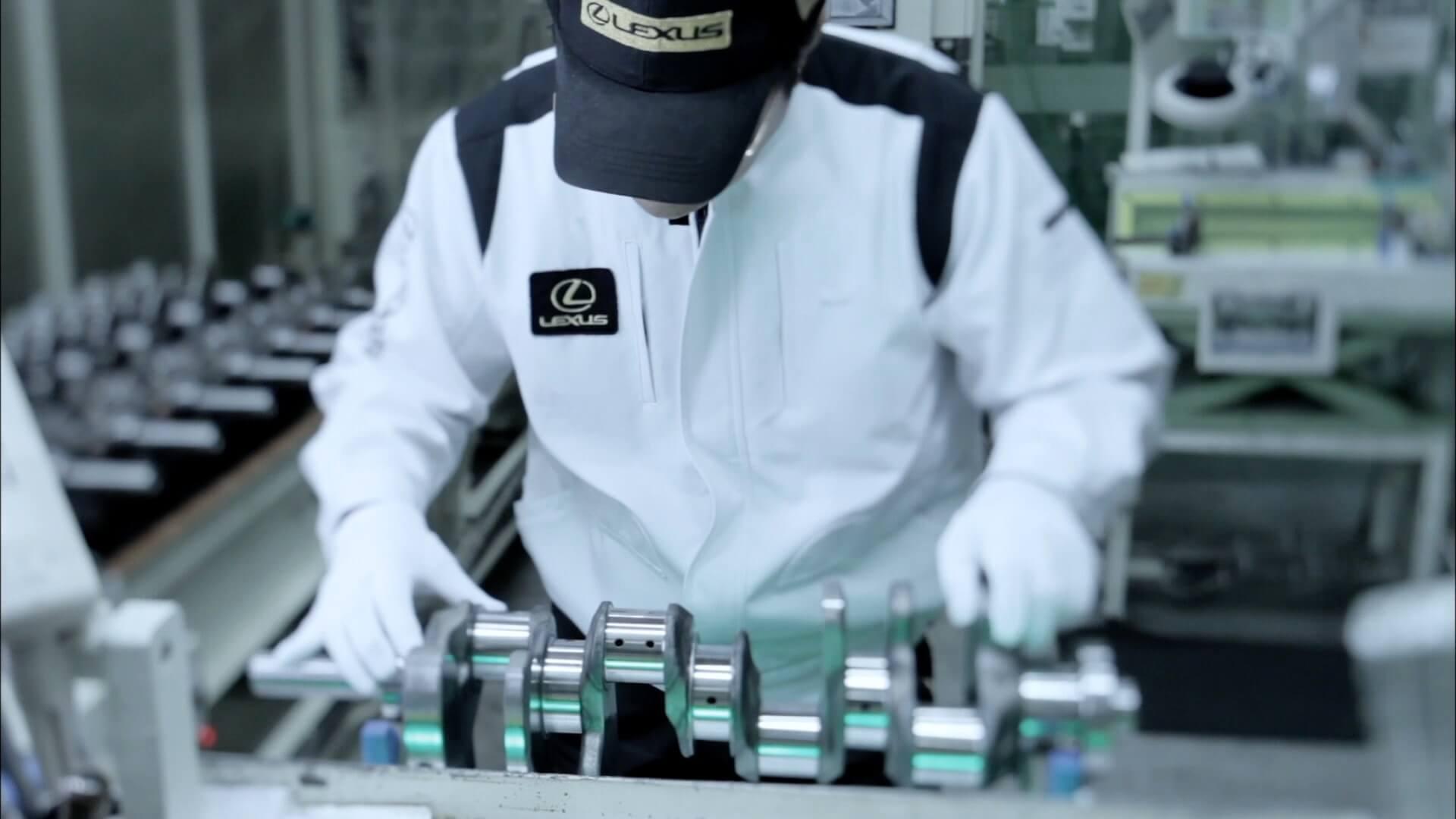 En Lexus Takumi mester kledd i hvitt med Lexus emblem på brystet